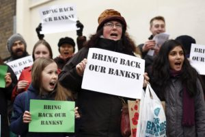 Bilde av protesterende gamle og unge med paroler Get Back Our Banksy